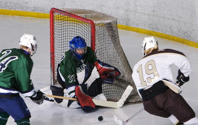 ice hockey players shooting at goal