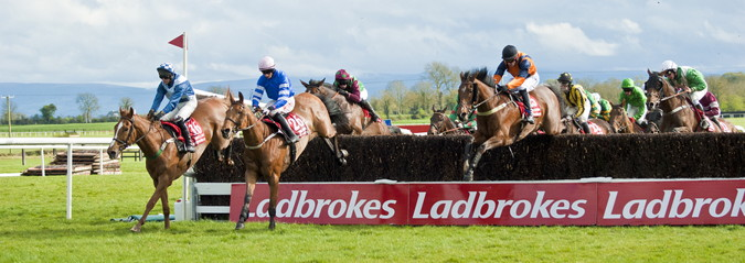 irish grand national horses jumping a fence
