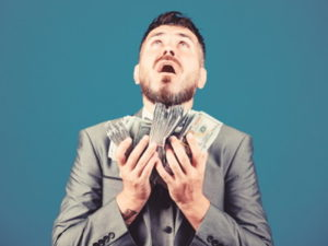 corporate man holding a lot of money looking up