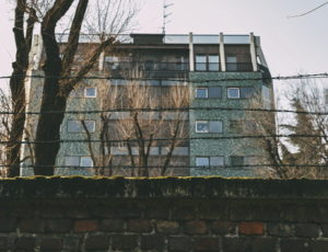 dilapidated tower block shown behind a wall with barbed wire