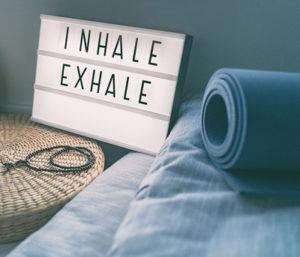 inhale exhale sign near yoga mat