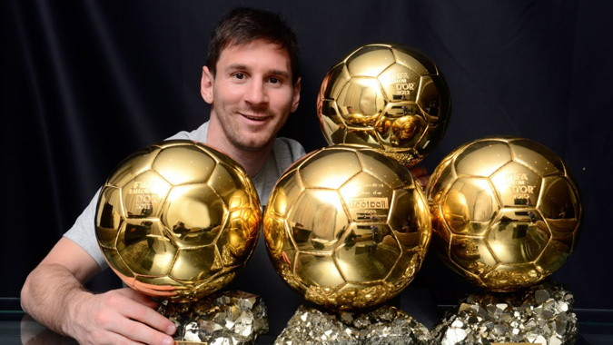 messi holding his ballon dor trophies