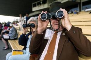 racing spectators viewing through binoculars