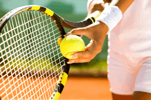 tennis player serving close up of bat and ball