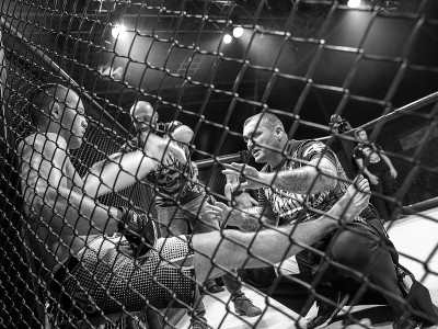 ufc fighter leaning against cage talking to trainer