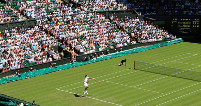 tennis player serving on centre court at wimbledon