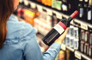 woman buying bottle of wine alcohol